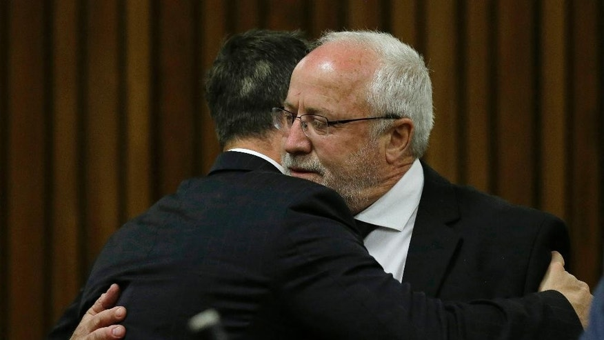 Oscar Pistorius is hugged by his estranged father, Henke Pistorius, right, as he arrives in court in Pretoria, South Africa, Tuesday, Oct. 21, 2014. Pistorius will finally learn his fate  when judge Thokozile Masipais is expected to announce the Olympic runner's sentence for killing girlfriend Reeva Steenkamp  (AP Photo/Themba Hadebe, Pool)