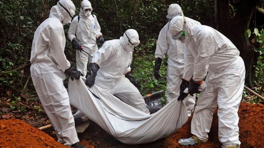 Oct. 20, 2014: Health workers bury the body of a woman who is suspected of having died of the Ebola virus in Bomi county, on the outskirts of Monrovia, Liberia.