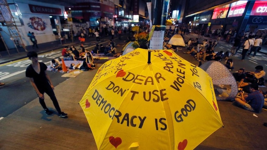 """An umbrella, which has become an icon of the protest, reads pro-democracy messages above the student-led protest site in the Mong Kok district of Hong Kong, Monday, Oct. 20, 2014. Hong Kong Chief Executive Leung Chun-ying has claimed that """"external forces"""" are participating in student-led pro-democracy protests that have occupied parts of this financial capital for more than three weeks, but provided no evidence to back his accusation.  (AP Photo/Wally Santana)"""