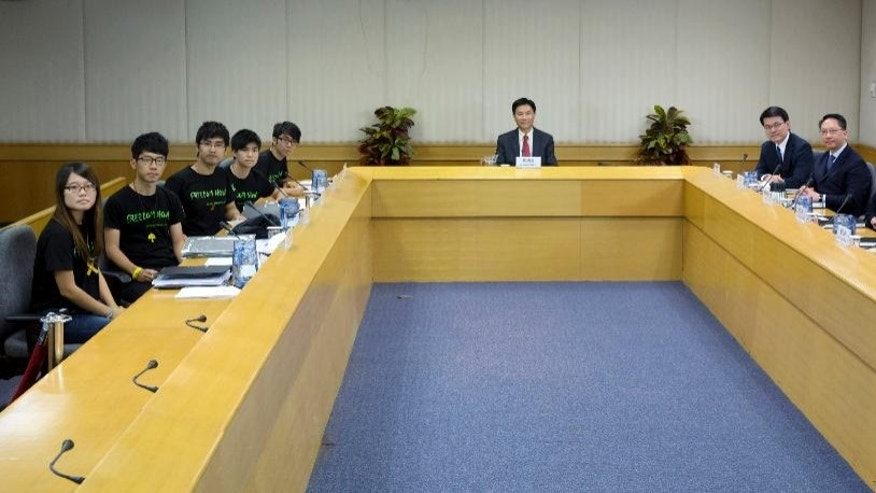 Hong Kong government officials, from right,  the Constitutional and Mainland Affairs Bureau Undersecretary Lau Kong-wah, Constitutional and Mainland Affairs Secretary Raymond Tam,  Chief Secretary for Administration Carrie Lam, Justice Secretary Rimsky Yuen and Chief Executive's Office Director Edward Yau Tang-wah, sit opposite to the student leaders from the Hong Kong Federation of Students, from fifth left to far left,  General Secretary Eason Chung, Deputy Secretary-General Lester Shum, Secretary-General Alex Chow, Council Members Nathan Law and Yvonne Leung during a photo call before their talks in Hong Kong Tuesday, Oct. 21, 2014. Hong Kong officials and student leaders hold talks Tuesday to try to end pro-democracy protests that have gripped the southern Chinese city for more than three weeks, though chances of success are slim given the vast differences between the two sides. The MC, center, is Lingnan University President Cheng Kwok Hon. (AP Photo/Kin Cheung)