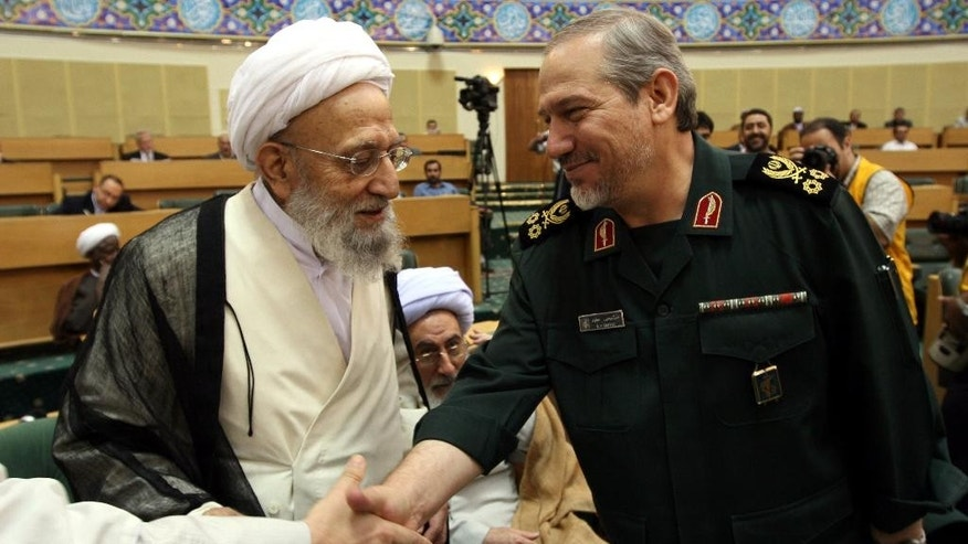 FILE - In this Saturday Aug. 18, 200 file photo, Commander-in-chief of Iran's elite Islamic Revolutionary Guards Corp, (IRGC) Major General Yahya Rahim Safavi, right, shakes hands with an unidentified cleric as senior cleric Ayatollah Mohammadreza Mahdavi Kani, stands at left, during a religious meeting in Tehran, Iran. Kani, the head of Iran's most influential clerical body charged with choosing or dismissing the country's supreme leader, has died. He was 83. (AP Photo/Hasan Sarbakhshian, File)