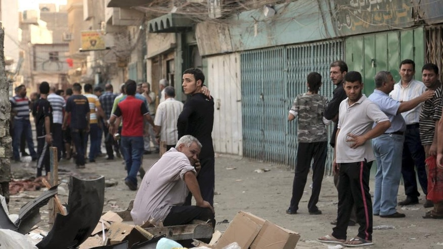 People look for their loved ones in front of al-Khairat Mosque after a suicide bomber blew himself up among Shiite worshippers after midday prayers as they were leaving the mosque, killing and wounding tens of people, in a commercial area of Baghdad, Iraq, Monday, Oct. 20, 2014. Militants unleashed attacks on Iraq's majority Shiite community on Monday the latest in relentless assaults that have challenged the Shiite-led government as it battles the Sunni-led insurgency by the Islamic State group. (AP Photo/Khalid Mohammed)