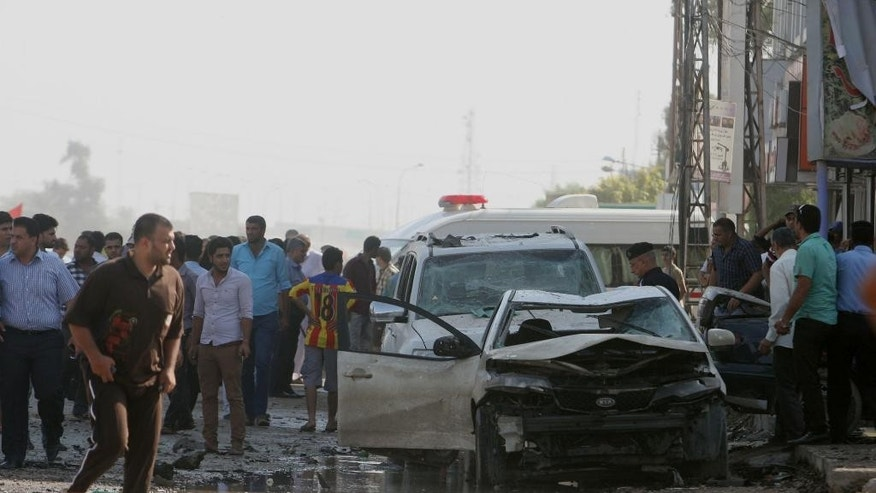Civilians gather at the scene of a car bomb explosion, killing and wounding tens of people, in a commercial area in the southern Shiite holy city of Karbala, 50 miles (80 kilometers) south of Baghdad, Iraq, Monday, Oct. 20, 2014. Militants unleashed attacks on Iraq's majority Shiite community on Monday the latest in relentless assaults that have challenged the Shiite-led government as it battles the Sunni-led insurgency by the Islamic State group. (AP Photo)