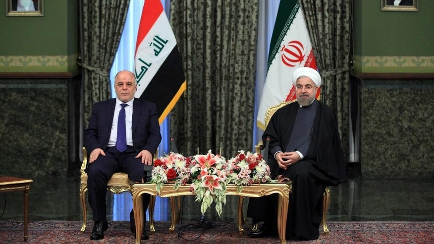 Iraqi Prime Minister Haidar al-Abadi, left, meets with Iran's President Hassan Rouhani, at Tehran's Saadabad Palace on Tuesday, Oct. 21, 2014. Rouhani said Iran will stand by its neighbor Iraq in its fight against the Sunni extremists of the Islamic State group and will continue to provide Baghdad with military advisers and weapons, according to a report by the official IRNA news agency.  He also criticized the U.S. for allegedly failing to sufficiently support Iraq. (AP Photo/Ebrahim Noroozi)