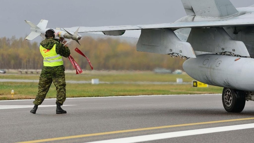 A member of the ground crew installs the protection pin onto a Canadian Air Force F-18 Hornet's missile at Siauliai Air Base in Lithuania Monday Oct. 20, 2014 .  Two Canadian F-18 Hornet jets were scrambled from the Siauliai Air Base in Lithuania on Monday to intercept a Russian Ilyushin-20 surveillance aircraft, which they shadowed for some 15 minutes, NATO said. (AP Photo/Canadian Air Force, Cpl Gabrielle DesRochers)
