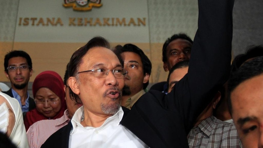 FILE - In this Friday, March 7, 2014 file photo, Malaysian opposition leader Anwar Ibrahim gestures as he leaves a courthouse in Putrajaya, Malaysia. Anwar said late Tuesday, Oct. 21, 2014 he expects Malaysia's top court will dismiss his final appeal against a sodomy conviction next week and that he will be sent to prison. Anwar was sentenced to five years in prison in March on charges of sodomizing a male aide after the appeals court overturned an earlier acquittal. The Federal Court will hear his appeal Oct. 28-29. (AP Photo/Lai Seng Sin, File)