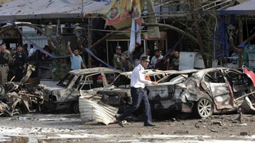 Oct. 21, 2014: Security forces and civilians inspect the site of a double car bomb attack that hit a restaurant in the Shiite-majority district of Talibiya in eastern Baghdad, Iraq.