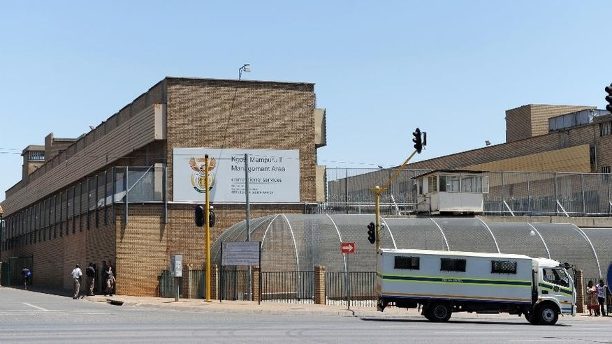 people walk outside the Kgosi Mampuru Correctional Services prison in Pretoria, South Africa, Tuesday, Oct. 21, 2014. Oscar Pistorius was sentenced to five years imprisonment at the facility by judge Thokozile Masipais for killing his girlfriend Reeva Steenkamp last year. (AP Photo)