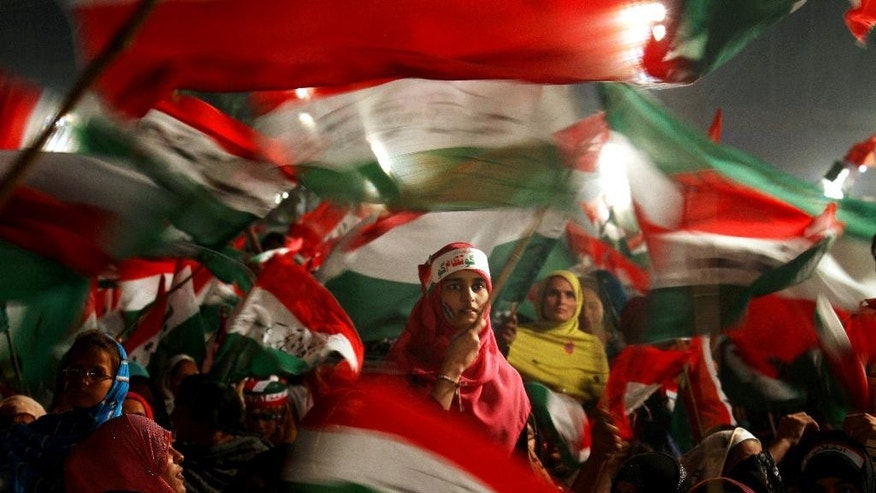 Women supporters of Pakistan's fiery cleric Tahir-ul-Qadri wave party flags as they take part in an anti government rally in Lahore, Pakistan, Sunday, Oct. 19, 2014. Thousands of anti-government protestors  led Muslim cleric Tahir-ul-Qadri rallied in Lahore demanding Prime Minister Nawaz Sharif's ouster over alleged fraud in last year's election. (AP Photo/K.M. Chaudary) (AP Photo/K.M. Chaudary)
