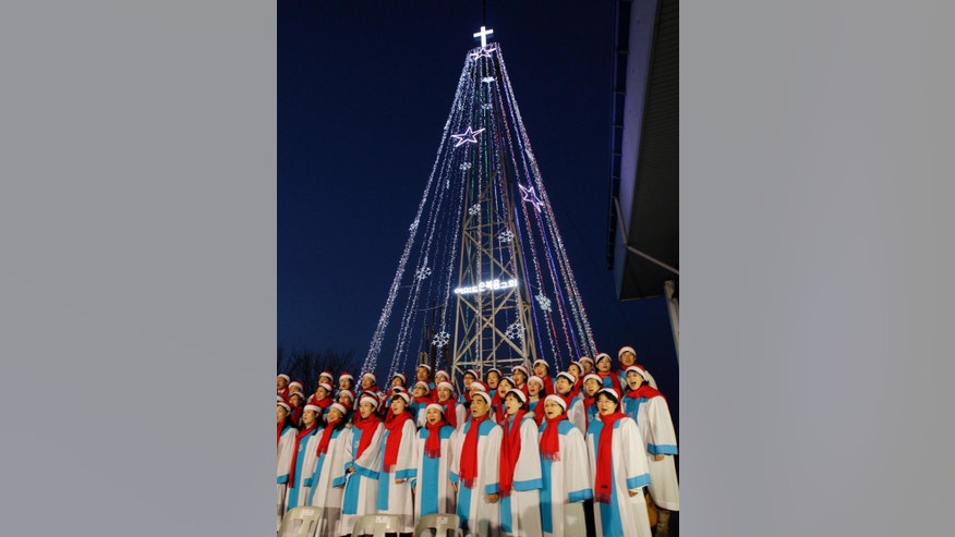 In this Tuesday, Dec. 21, 2010, South Korean Christians sing a Christmas song in front of a giant steel Christmas tree at the western mountain peak known as Aegibong in Gimpo, South Korea. An official from Seoul's Defense Ministry said Wednesday that the 18-meter structure was demolished last week after it was reviewed as dangerous in a safety inspection. The tower was erected on a military-controlled hill called Aegibong in 1971. The lighting of the tower was condemned by Pyongyang as propaganda as the lights can be seen as far as the North Korean city of Kaesong. (AP Photo/Lee Jin-man)