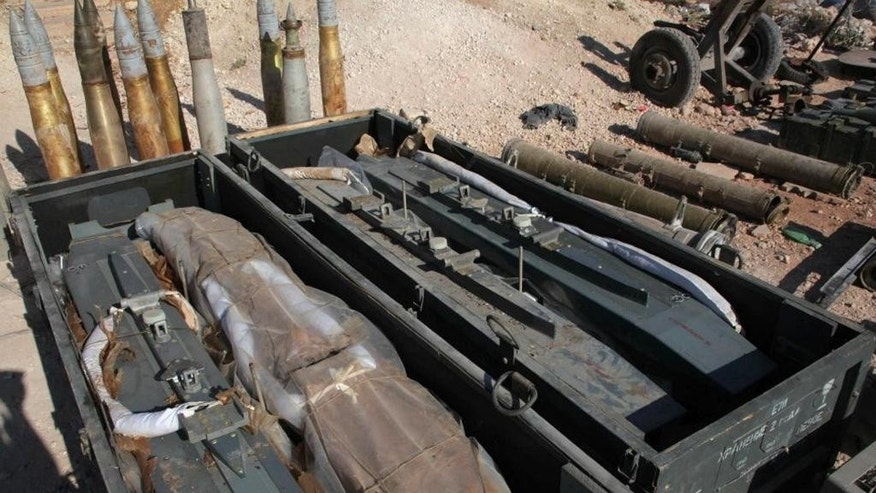 This Sunday July 6, 2014 file photo released by the Syrian official news agency SANA, shows weapons that SANA says were captured by Syrian government forces in Kafr Saghir, outside Aleppo, Northern Syria.  Syrian President Bashar Assad is taking advantage of the U.S.-led coalition's war against the Islamic State group to pursue a withering air and ground campaign against more mainstream rebels elsewhere in the country, trying to recapture areas considered more crucial to the survival of his government. Assad's troops are now focusing their energies on the country's two largest cities, Damascus and Aleppo. (AP Photo/SANA, File)