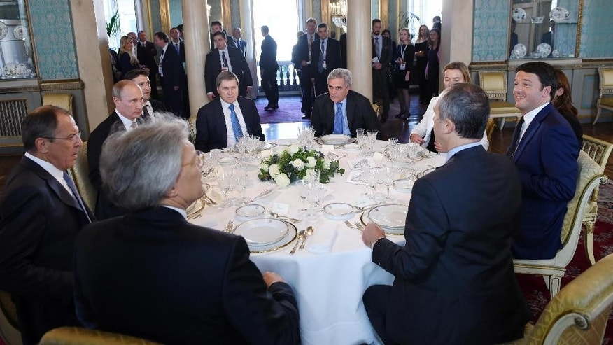 Italian Prime Minister Matteo Renzi, right, and Russian President Vladimir Putin lunch together after a meeting on the sidelines of the ASEM summit of European and Asian leaders in Milan, northern Italy, Friday, Oct. 17, 2014. Russian leader Vladimir Putin was meeting with Ukrainian President Petro Poroshenko and key Western leaders in an attempt to negotiate a full end to hostilities in Ukraine that could ease sanctions against Russia. (AP Photo/Daniel Dal Zennaro, POOL)