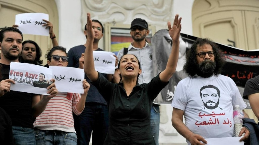 FILE - This file photo dated May 22, 2014, shows Tunisian activists staging a demonstration in front of the Tunis courthouse in Tunisia in support of a jailed blogger. The arrest for drug possession of Aziz Amami, a prominent blogger from the 2011 revolution that overthrew Tunisia's police state, prompted protests and a renewed effort to amend draconian drug laws that many say are used by police to abuse their enemies. On Sunday, Tunisians are set to vote in parliamentary elections that will nearly complete the democratic transition begun by the revolution, but many fear the bad old ways are creeping back. Just on Sept. 27 and Oct. 3, two more young men died in police custody under suspicious circumstances. (AP Photo/Ilyess Osmane, File)