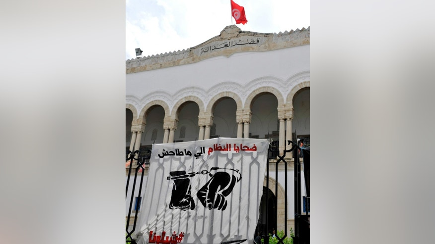 FILE - This photo dated May 23, 2014, shows banners hanging on the fence of the Tunis courthouse in Tunisia, in support of a blogger. The arrest for drug possession of Aziz Amami, a prominent blogger from the 2011 revolution that overthrew Tunisia's police state, prompted protests and a renewed effort to amend draconian drug laws that many say are used by police to abuse their enemies. On Sunday, Tunisians are set to vote in parliamentary elections that will nearly complete the democratic transition begun by the revolution, but many fear the bad old ways are creeping back. Just on Sept. 27 and Oct. 3, two more young men died in police custody under suspicious circumstances. (AP Photo/Ilyess Osmane, File)