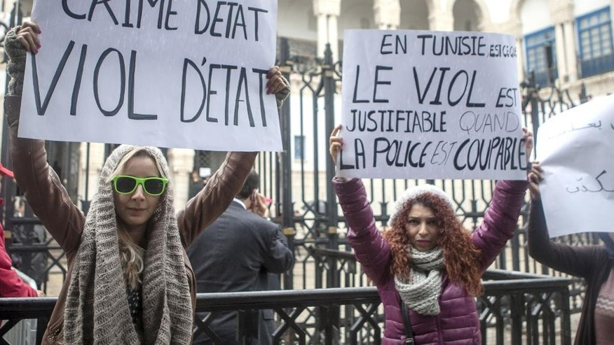 "FILE - In this file photo dated Monday, March 31, 2014, Tunisian women demonstrate outside a courthouse where three police officers face charges of rape of a 27-year-old woman, in Tunis, Tunisia. The 27-year-old woman says three police officers stopped her in a car in September, and one of them held her fiance back while the other two raped her.  The police officers deny wrongdoing, and allege the couple had been engaged in ""immoral"" behavior. Posters read: at left, 'State Crime, State Rape', and at right 'Rape is right when police is guilty'. On Sunday, Tunisians are set to vote in parliamentary elections that will nearly complete the democratic transition begun by the revolution, but many fear the bad old ways are creeping back. Just on Sept. 27 and Oct. 3, two more young men died in police custody under suspicious circumstances. (AP Photo/Aimen Zine, File)"