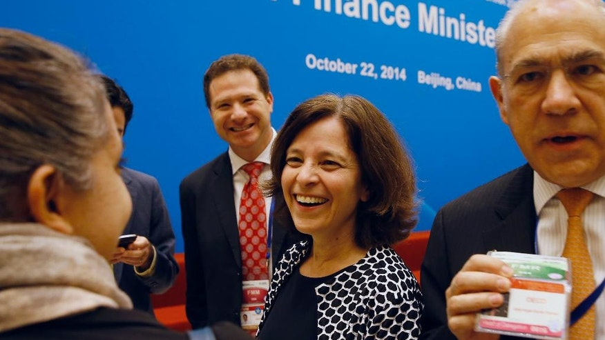 U.S. Deputy Treasury Secretary Sarah Bloom Raskin, center, chats with her delegations as they arrive for the opening ceremony of the Asia-Pacific Economic Cooperation (APEC) finance ministers meeting at the Diaoyutai State Guesthouse in Beijing, China Wednesday, Oct. 22, 2014. (AP Photo/Andy Wong)