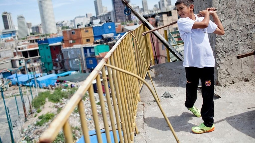 In this Tuesday, Oct. 21, 2014 photo, Dylan Reales poses for a photo with his first golf stick, a makeshift golf club made from a wooden broom stick, on the terrace of his home, in Buenos Aires, Argentina. Reales started learning to play golf by swinging the broken broomstick at fruit and vegetables discarded at a temporary market set up in front of his house in one of the poorest neighborhoods in Buenos Aires. (AP Photo/Natacha Pisarenko)