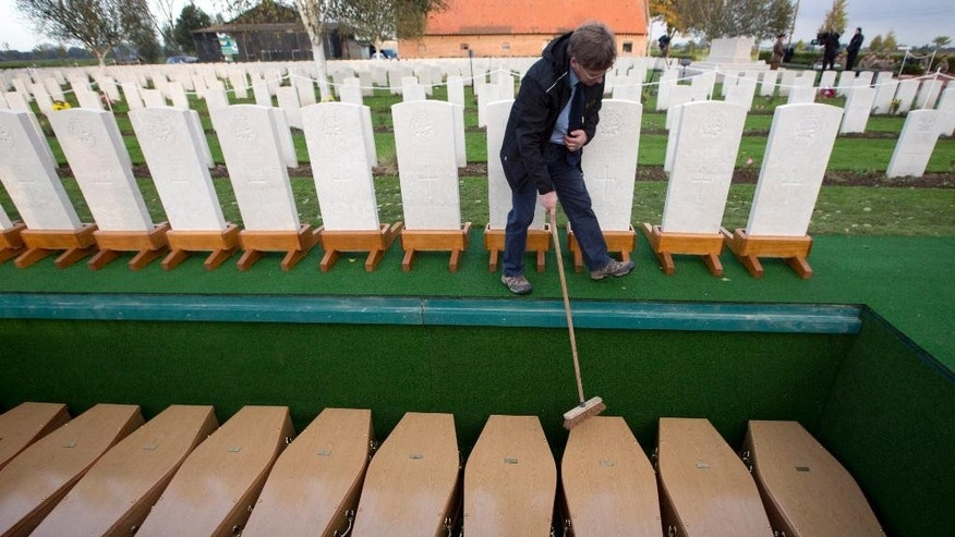A worker from the Commonwealth War Graves Commission cleans leaves off of the caskets of World War I soldiers prior to a re-burial ceremony in Bois-Grenier, France, Wednesday, Oct. 22, 2014. Fifteen British WWI soldiers were re-buried at Y Farm Commonwealth cemetery on Wednesday, nearly a century after they died in battle. The soldiers, who served with the 2nd Battalion, York and Lancaster Regiment, were discovered in a field nearby in Beaucamps-Ligny in 2009 and identified through a variety of means, including DNA. (AP Photo/Virginia Mayo)