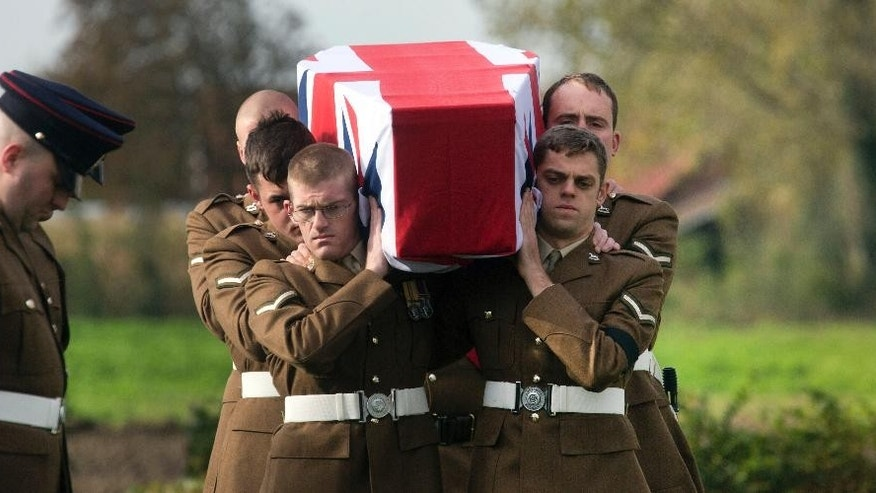 Two British soldiers bow their heads as a detail carry the casket of a World War I soldier during a re-burial ceremony in Bois-Grenier, France, Wednesday, Oct. 22, 2014. Fifteen British WWI soldiers were re-buried at Y Farm Commonwealth cemetery on Wednesday, nearly a century after they died in battle. The soldiers, who served with the 2nd Battalion, York and Lancaster Regiment, were discovered in a field nearby in Beaucamps-Ligny in 2009 and identified through a variety of means, including DNA. Out of the 15 soldiers found, 11 were positively identified. (AP Photo/Virginia Mayo)