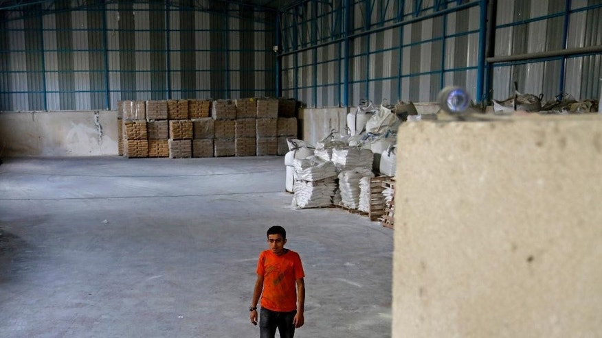 A Palestinian worker walks by a security camera, seen at upper right, that was installed to watch construction materials and for U.N. monitors to inspect periodically to make sure they are not diverted by Hamas for military use, while working in Shijaiyah neighborhood in Gaza City in the northern Gaza Strip, Wednesday, Oct. 22, 2014. Several dozen tons of cement bags stored in a warehouse are one of the few tangible achievements so far of a $2.7 billion plan to rebuild war-wrecked Gaza Strip. The program was launched with high expectations at an international conference in Cairo on Oct. 12, but has run into obstacles, including wrangling between the rival Palestinian factions Hamas and Fatah for control in Gaza and what officials say has been a trickle of promised aid. (AP Photo/Adel Hana)