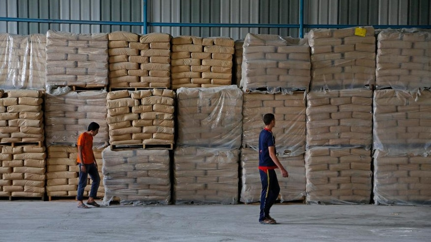 Palestinian workers check bags of cement at a warehouse with security cameras to watch construction materials and for U.N. monitors to inspect periodically to make sure they are not diverted by Hamas for military use, while working in Shijaiyah neighborhood in Gaza City in the northern Gaza Strip, Wednesday, Oct. 22, 2014. Several dozen tons of cement bags stored in a warehouse are one of the few tangible achievements so far of a $2.7 billion plan to rebuild war-wrecked Gaza Strip. The program was launched with high expectations at an international conference in Cairo on Oct. 12, but has run into obstacles, including wrangling between the rival Palestinian factions Hamas and Fatah for control in Gaza and what officials say has been a trickle of promised aid. (AP Photo/Adel Hana)