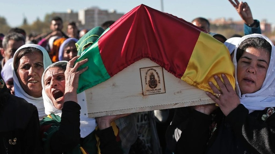 Mourners carry the coffin with the body of female Kurdish fighter Hanim Dabaan, 20, killed in the fighting with the militants of the Islamic State group in Kobani, Syria, during the funeral of three fighters, at a cemetery in Suruc, on the Turkey-Syria border, Tuesday, Oct. 21, 2014. The three fighters were killed during the last few days battling Islamic State group  fighters in the Kurdish Syrian town of Kobani, also known as Ayn Arab,located on the border with Turkey. They were buried without their families present; in the chaos of war, since mid-September, hundreds of thousands of Kurds have become refugees, and contacting the families of those killed is not always possible. (AP Photo/Lefteris Pitarakis)