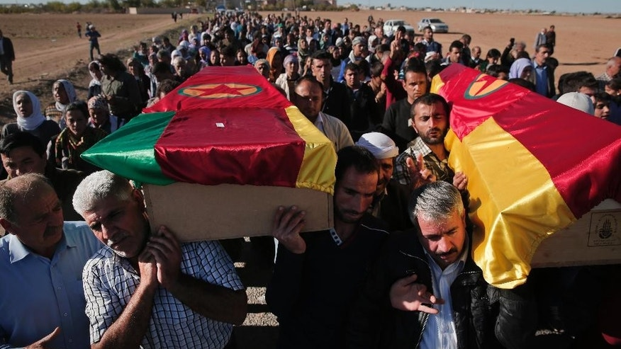 Mourners carry the coffins with the bodies of Kurdish fighters Idris Ahmad, 30, right, and Mohammed Mustafa, 25, left, killed in the fighting with the militants of the Islamic State group in Kobani, Syria, during the funeral of three fighters, at a cemetery in Suruc, on the Turkey-Syria border, Tuesday, Oct. 21, 2014. The three fighters were killed during the last few days battling  fighters of the Islamic State group in the Kurdish Syrian town of Kobani, also known as Ayn Arab,located on the border with Turkey. They were buried without their families present; in the chaos of war, since mid-September, hundreds of thousands of Kurds have become refugees, and contacting the families of those killed is not always possible. (AP Photo/Lefteris Pitarakis)