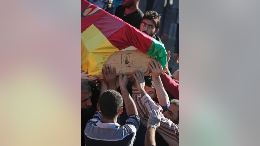 Mourners carry the coffin with the body of Kurdish fighter Idris Ahmad, 30, killed in the fighting with the militants of the Islamic State group in Kobani, Syria, during the funeral of three fighters, at a cemetery in Suruc, on the Turkey-Syria border, Tuesday, Oct. 21, 2014. The three fighters were killed during the last few days battling fighters of the Islamic State group in the Kurdish Syrian town of Kobani, also known as Ayn Arab,located on the border with Turkey. They were buried without their families present; in the chaos of war, since mid-September, hundreds of thousands of Kurds have become refugees, and contacting the families of those killed is not always possible. (AP Photo/Lefteris Pitarakis)