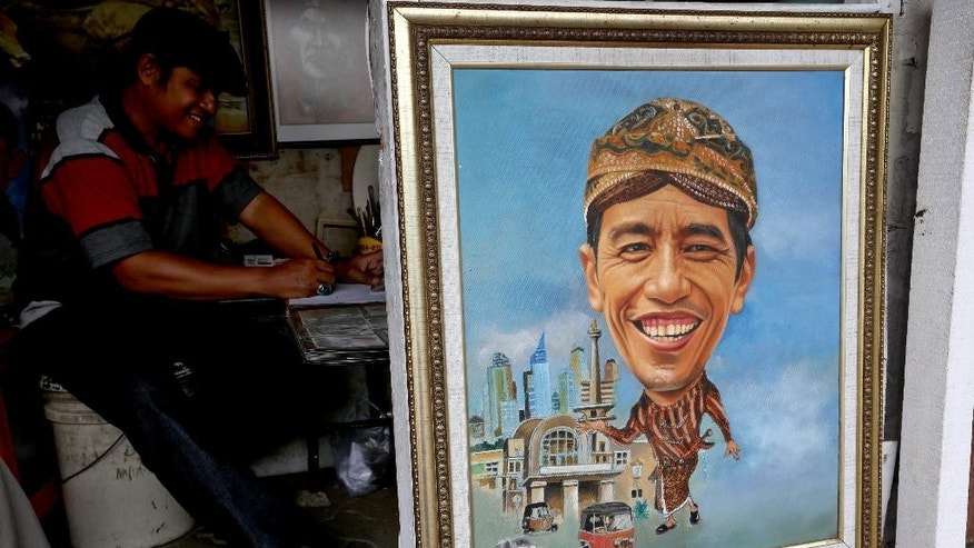 A painting of new Indonesian President Joko Widodo is displayed at his street-side kiosk in Jakarta, Indonesia, Tuesday, Oct. 21, 2014. Widodo, popularly known as 'Jokowi' was inaugurated as the country's seventh president on Oct. 20.(AP Photo/Tatan syuflana)