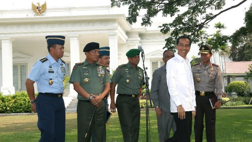 Indonesian President Joko Widodo, second from right, smiles during a press conference with military top brass, from left to right, Air Force Chief of Staff Air Marshall Ida Bagus Putu Dunia, Armed Forces Chief Gen. Moeldoko, Navy Chief of Staff Adm. Marsetio, Army Chief of Staff Gen. Gatot Nurmantyo, Head of State Intelligence Agency Marciano Norman and National Police Chief Gen. Sutarman, at the presidential palace in Jakarta, Indonesia, Wednesday, Oct.  22, 2014. Indonesia's new president says he wants to be called by his nickname, and has revealed who first gave it to him: a French furniture buyer. (AP Photo/Tatan Syuflana)