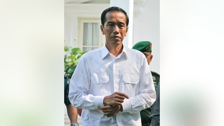 Indonesian President Joko Widodo walks to attend a press conference at the presidential palace in Jakarta, Indonesia, Wednesday, Oct.  22, 2014. Indonesia's new president says he wants to be called by his nickname, and has revealed who first gave it to him: a French furniture buyer. (AP Photo/Tatan Syuflana)