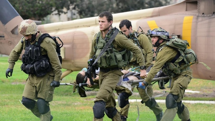 Israeli soldiers carry a comrade who was wounded in an attack on the border with Egypt to a hospital in Beersheba, Israel, Wednesday, Oct. 22, 2014. Attackers from the Egyptian side of the border fired an anti-tank missile and gunshots at an Israeli military vehicle on Wednesday, wounding two soldiers in a rare cross-border incident,  the Israeli military said. The Israeli military said it has no indication yet who was behind the attack. (AP Photo/Dudu Grunshpan)  ***ISRAEL OUT***
