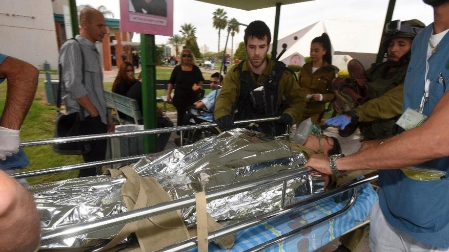 An Israeli soldier who was wounded in an attack on the border with Egypt is brought to a hospital in Beersheba, Israel, Wednesday, Oct. 22, 2014. Attackers from the Egyptian side of the border fired an anti-tank missile and gunshots at an Israeli military vehicle on Wednesday, wounding two soldiers in a rare cross-border incident,  the Israeli military said. (AP Photo/Dudu Grunshpan)  ***ISRAEL OUT***