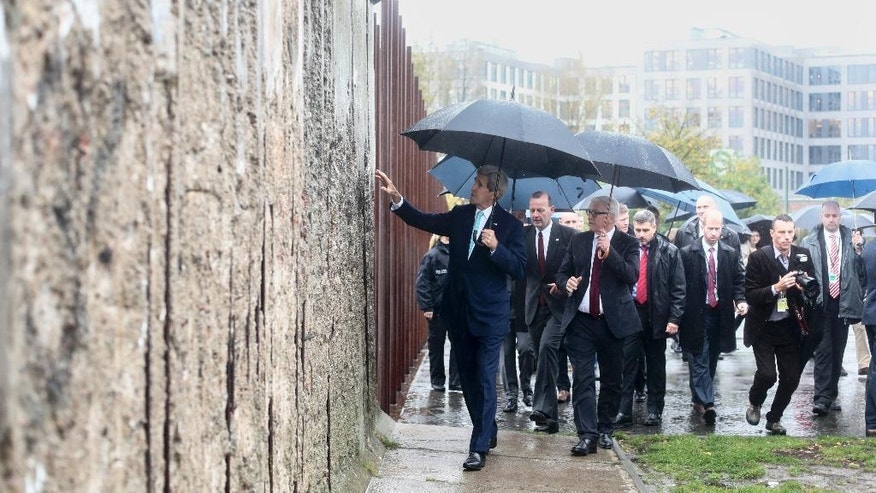 United States Secretary of State John Kerry, left, touches the remains of the  Berlin Wall during a visits at the Wall memorial site prior to a news conference with German Foreign Minister Frank-Walter Steinmeier , third left, in Berlin, Wednesday, Oct. 22, 2014.  (AP Photo/Markus Schreiber, Pool)