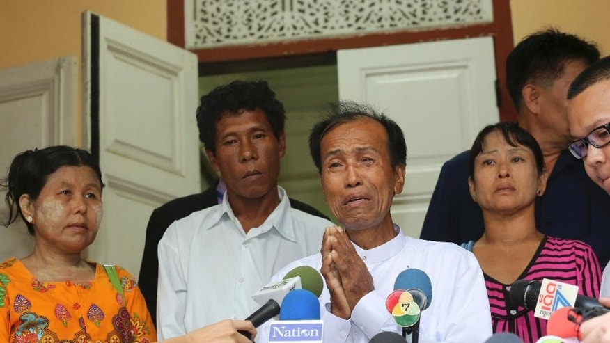 Tun tun Htike, center, father of arrested Myanmar migrant worker Win Zaw Htun, cries while addressing the media as Thing Shwe Aug, left, Phu Shwe Nu, second from left, parents of Zaw Lin  and May Thein , mother of Win Zaw Htun listen at the Myanmar Embassy in Bangkok ,Thailand Wednesday, Oct. 22, 2014. Myanmar migrant workers Win Zaw Htun and Zaw Lin have retracted their confessions to killing two British travelers on a southern Thai resort island and now claim to have neither raped the female victim nor slain the pair, the men's lawyers said Wednesday.(AP Photo/Sakchai Lalit)