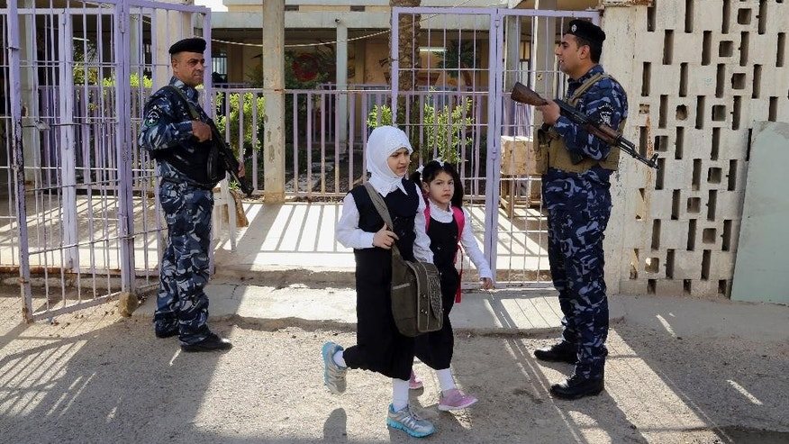 Policemen stand guard as Iraqi students leave al-Kenuz primary school in Baghdad, Iraq, Wednesday, Oct. 22, 2014. Iraqi students went back to school on Wednesday amid tightened security as the academic year began a month late because thousands of people displaced by last summer's onslaught by the Islamic State group had taken shelter in school buildings. (AP Photo/Karim Kadim)