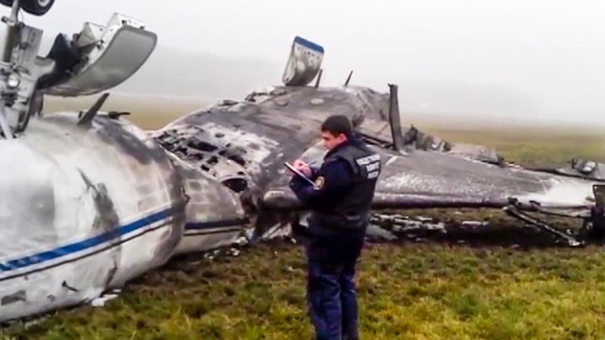 In this image made from video provided by Russian State Television Rossiya, an investigator works at the wreckage of a private jet which collided with a snowplow at Vnukovo airport in Moscow, Tuesday, Oct. 21, 2014. The head of French oil giant Total SA and three French crew members were killed at Vnukovo airport when a corporate jet, the French-made Dassault Falcon 50, collided with a snowplow, Russian investigators said Tuesday. (AP Photo) TV OUT