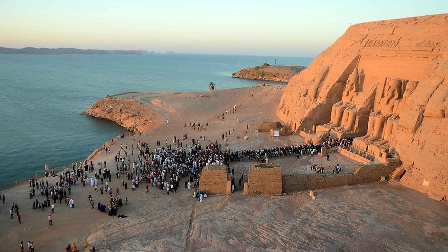 People visit the Great Temple of Ramses II to observe the sun to send a beam of light into the ancient temple's dark inner chamber for over ten minutes in Abu Simbel, 870 kilometers (540 miles) south of Cairo, Egypt, Wednesday, Oct. 22, 2014. Hundreds of people visited the temple to watch the sun illuminate colossal statues, a rare 3,200-year-old astronomical ceremony that happens twice a year. (AP Photo/Ibrahim Zayed)