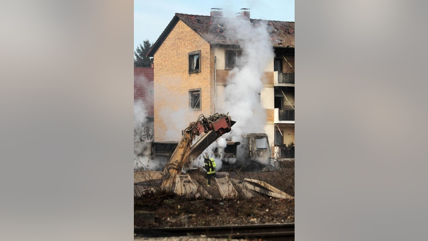 A firefighter is busy at the site were an explosion happened after a gas pipe was damaged during construction work in Ludwigshafen, western Germany, Thursday, Oct. 23, 2014. One person was killed in the explosion and several others were injured. (AP Photo/dpa, Fredrik von Erichsen)