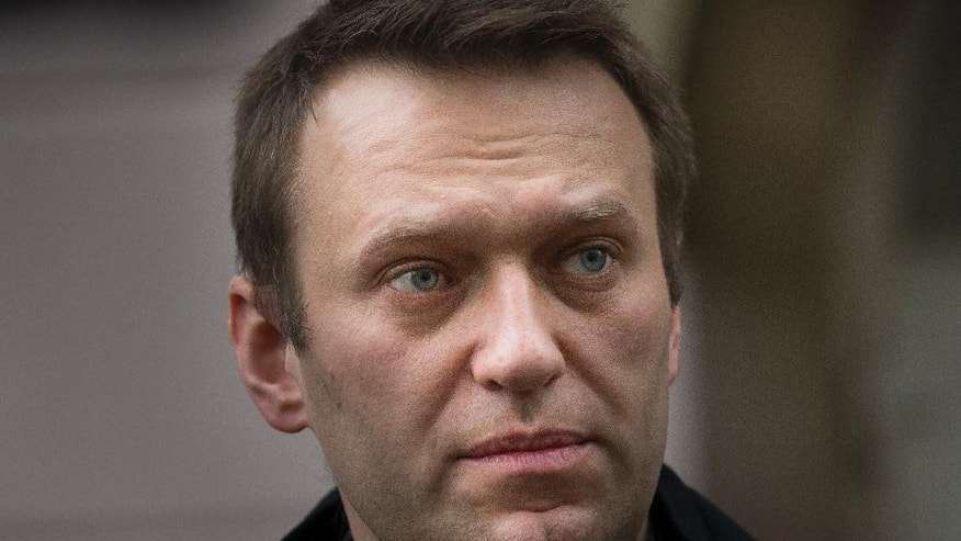 In this photo taken Tuesday, Oct. 21, 2014, Russian opposition activist Alexei Navalny, who has been under house arrest for nearly eight months, leaves a district court in Moscow, Russia. Two years ago, Navalny was the charismatic driving force behind massive anti-government protests in Moscow. Now he wears a monitoring bracelet on his ankle and is not allowed to step over the threshold of his own home - under house arrest in the small apartment he shares with his wife and two children. (AP Photo/Alexander Zemlianichenko)