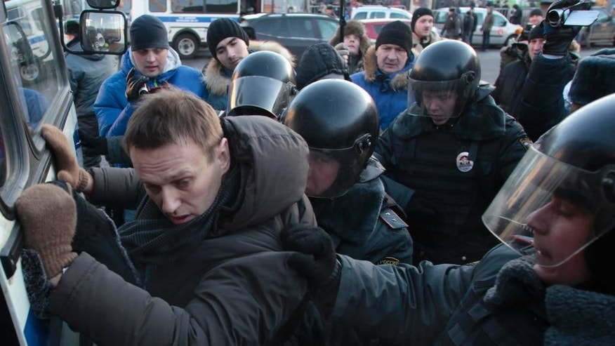 FILE - In this Saturday, Dec. 15, 2012 file photo, police officers detain opposition leader Alexei Navalny during an unauthorized rally in Lubyanka Square in Moscow, Russia. Two years ago, Navalny was the charismatic driving force behind massive anti-government protests in Moscow. Now he wears a monitoring bracelet on his ankle and is not allowed to step over the threshold of his own home - under house arrest in the small apartment he shares with his wife and two children. (AP Photo/Pavel Golovkin, File)