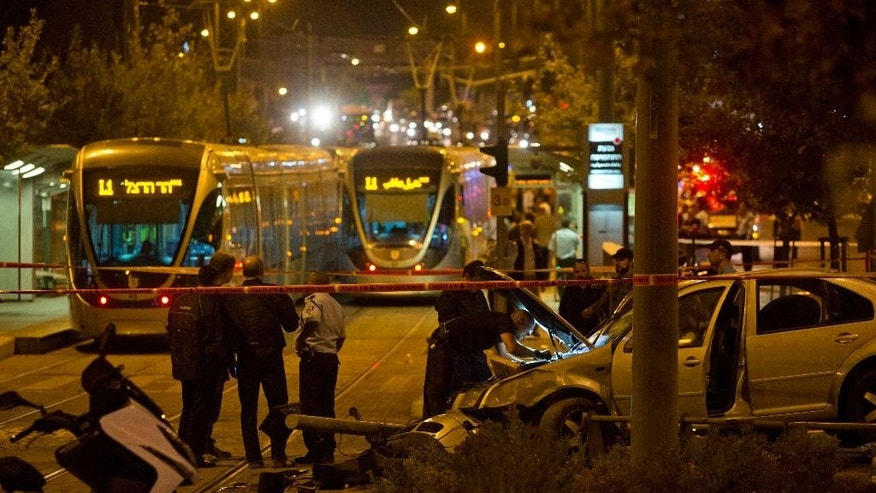 Oct. 22, 2014: Israeli police officers inspect a car at the scene of an attack in Jerusalem. (AP)