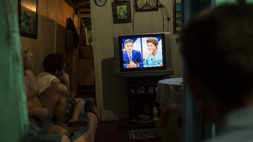 In this Oct. 16, 2014 photo, residents in their home watch a live presidential debate on TV between candidates Aecio Neves, left, and Brazil's current President Dilma Rousseff in the Dona Marta slum of Rio de Janeiro, Brazil, ahead of a presidential election run-off on Sunday, Oct. 26. The tightest and most unpredictable presidential election since Brazil's return to democracy three decades ago is now in the hands of lower middle class voters who remain torn about which candidate they'll back just days before the ballot. (AP Photo/Felipe Dana)