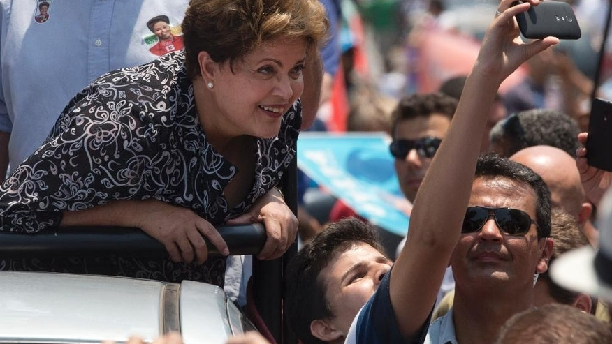 In this Oct. 20, 2014 photo, Brazil's President and Workers Party candidate Dilma Rousseff poses for a photo with a supporter during a rally for her re-election campaign in Rio de Janeiro, Brazil. The tightest and most unpredictable presidential election since Brazil's return to democracy three decades ago is now in the hands of lower middle class voters who represent 35 percent of the electorate and remain torn about which candidate they'll back just days before the ballot. Which camp such voters ultimately fall in has wavered over the final days of the campaign. (AP Photo/Silvia Izquierdo)