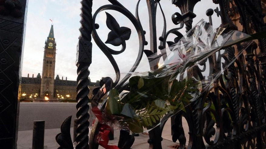 A rose rests in the main gate of Parliament Hill in Ottawa on Thursday, October 23, 2014. Cpl. Nathan Cirillo was killed Wednesday at the National War Memorial by a gunman who then raced to Parliament Hill, where he was killed in a gunfight in the halls of the Centre Block. (AP Photo/The Canadian Press, Adrian Wyld)