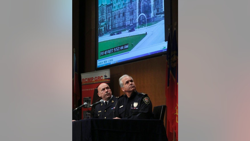 Royal Canadian Mounted Police Commissioner Bob Paulson, left, and Ottawa Police Chief Charles Bordeleau watch surveillance video from yesterday's shooting on Parliament Hill at a press conference at the RCMP Headquarters in Ottawa on Thursday, Oct. 23, 2014. (AP Photo/The Canadian Press, Patrick Doyle)