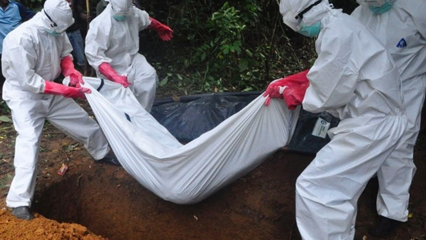 Oct. 18, 2014, a burial team in protective gear buries a person suspected to have died of Ebola in Monrovia, Liberia. Even as Liberians get sick and die of Ebola, many beds in treatment centers are empty because of the governments order that the bodies of all suspected Ebola victims be cremated.