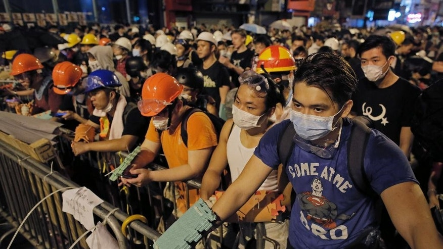 In this Sunday, Oct. 19, 2014 photo, protesters guard makeshift barricades at a pro-democracy protest encampment in the Mong Kok district of Hong Kong. As thousands of protesters block city streets demanding democratic reforms, the future of Hong Kong's exclusive - some would say purposefully opaque - election committee may prove key to defusing a high-stakes political standoff that has dragged on for nearly a month.   (AP Photo/Vincent Yu)