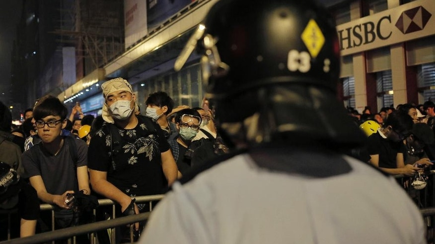 In this Sunday, Oct. 19, 2014 photo, protesters guard against riot police in front of a makeshift barricade at a pro-democracy protest encampment in the Mong Kok district of Hong Kong. As thousands of protesters block city streets demanding democratic reforms, the future of Hong Kong's exclusive - some would say purposefully opaque - election committee may prove key to defusing a high-stakes political standoff that has dragged on for nearly a month.  (AP Photo/Vincent Yu)