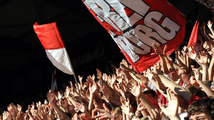 In this photo taken Saturday, Oct. 18, 2014, fans raise their arms in unison in the standing area of Freiburg's Schwarzwald Stadium during the team's 2-1 loss at home to Wolfsburg, in Freiburg, Germany. As one of the Bundesliga's most financially disadvantaged teams, Freiburg deploys an array of coping strategies to stay in Germany's top division and remain competitive against rivals like Wolfsburg that have richer resources, revenues and budgets. (AP Photo/John Leicester)